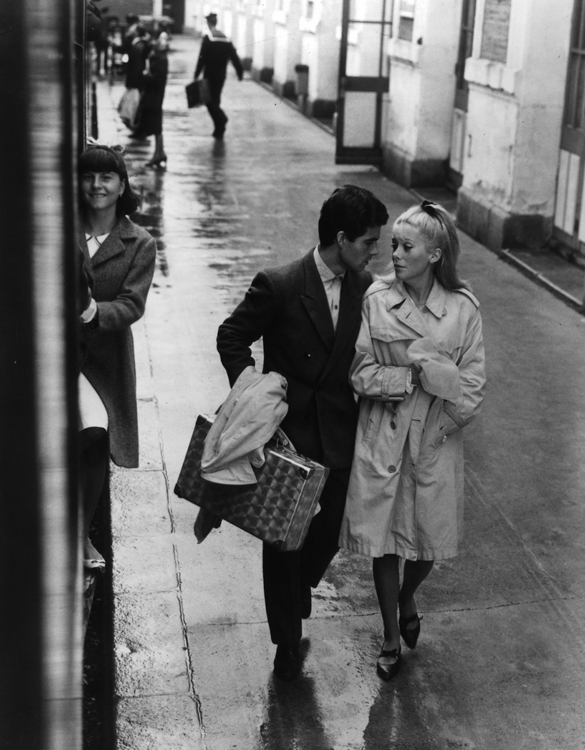 nino-castelnuovo-and-catherine-deneuve-walk-down-a-wet-sidewalk-in-a-scene-from-the-film-the-umbrellas-of-cherbourg-1964-photo-by-landau-releasing-organizationgetty-images
